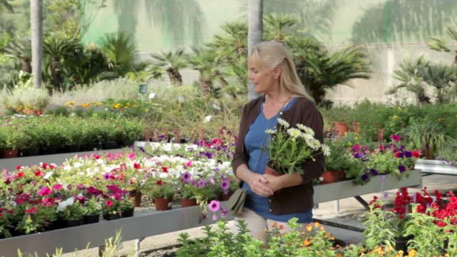 mature woman in garden centre - centro per il giardinaggio video stock e b–roll