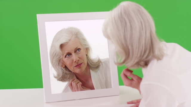 mature woman in her 50s checking her reflection in the mirror on greenscreen - vanity stock videos & royalty-free footage