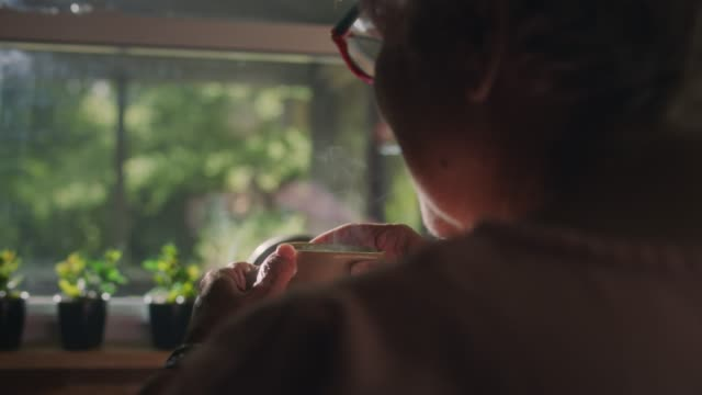 vídeos de stock e filmes b-roll de cu slo mo. mature woman in home kitchen holds a hot cup of coffee and steam rises in the morning light. - diário