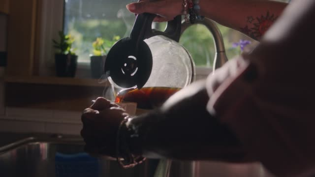 cu slo mo. mature woman in home kitchen pours a steaming cup of coffee in the morning. - hushållsapparat bildbanksvideor och videomaterial från bakom kulisserna