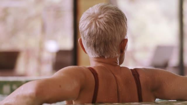 vidéos et rushes de femme d'âge mûr dans le jacuzzi, vue arrière - établissement de cure