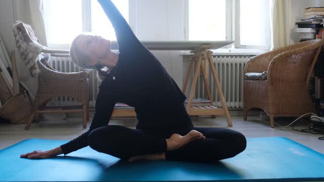 reife frau in sportbekleidung training zu hause - pilates stock-videos und b-roll-filmmaterial