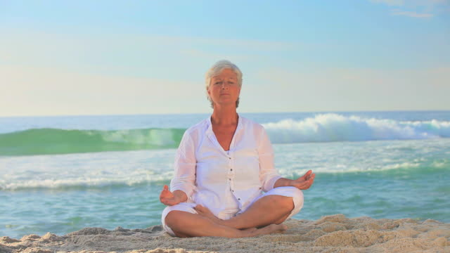 mature woman in white doing yoga / cape town, western cape, south africa - 祈りのポーズ点の映像素材/bロール