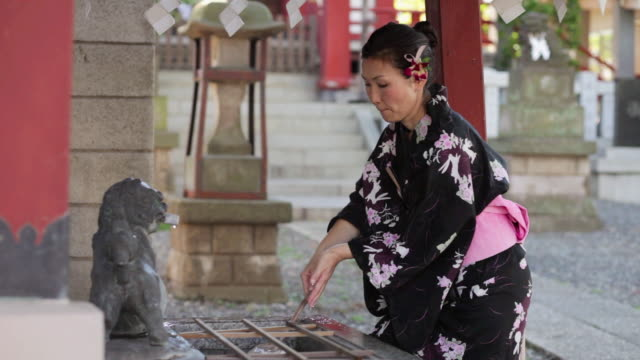 MS Mature woman in yukata (Japanese costume) is at shrine's chozubachi (water basin) and uses water dippers to purify herself before entering shrine / Tokyo, Japan