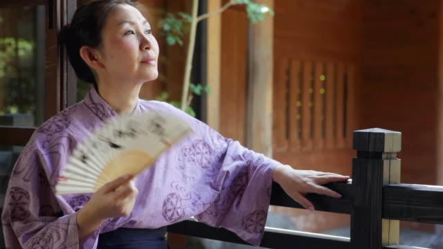 ms mature woman in yukata (japanese costume) relaxing and holding fan at traditional house / yufuin, oita, japan - yukata video stock e b–roll