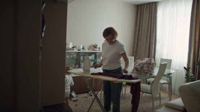 mature woman ironing clothes in living room - ironing board stock videos & royalty-free footage