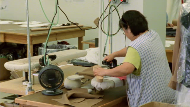 MS PAN Mature woman ironing garment on industrial-sized ironing board / New York City, New York, USA