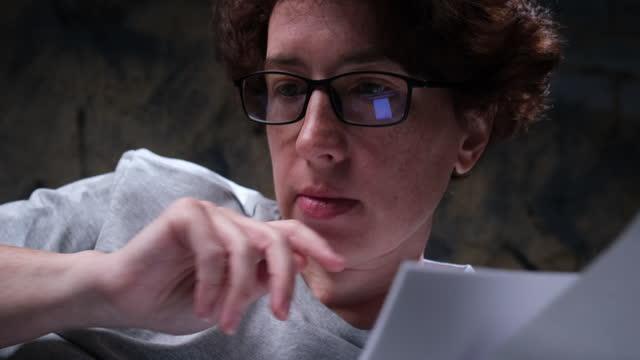 reife frau überprüft ihre finanziellen rechnungen mit laptop im bett - one mature woman only stock-videos und b-roll-filmmaterial