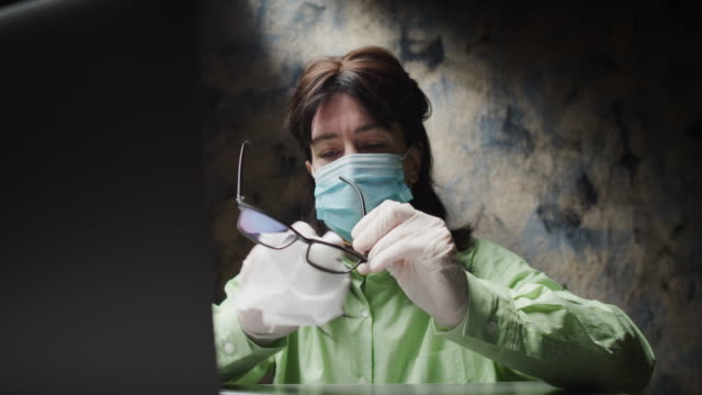 mature woman is cleaning her eyeglasses for it getting wet because of wearing face mask - eyewear stock videos & royalty-free footage