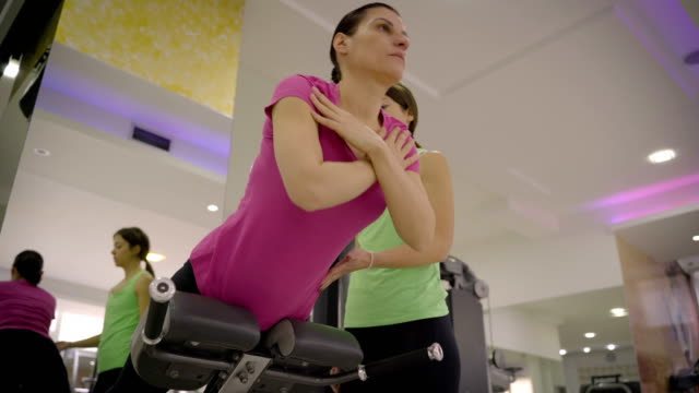 mature woman is doing a back exercise with her coach - durevolezza video stock e b–roll