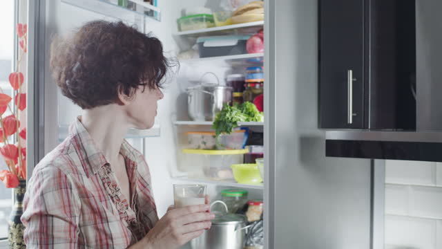 mature woman is drinking buttermilk next to the fridge - buttermilk stock videos & royalty-free footage
