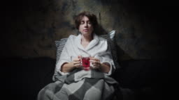 Mature woman is drinking herbal tea before sleep