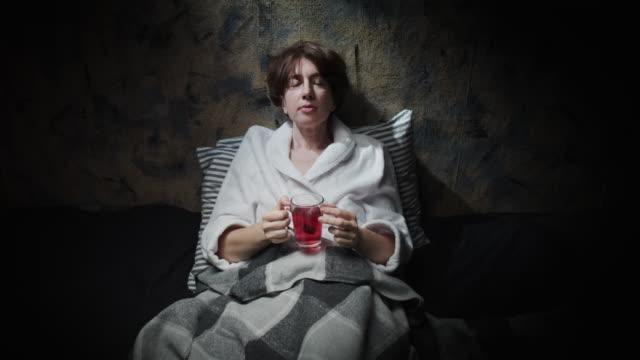 mature woman is drinking herbal tea before sleep - bathrobe stock videos & royalty-free footage