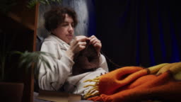 Mature woman is knitting while sitting on the sofa