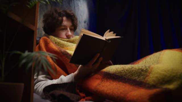 vidéos et rushes de la femme mûre lit un livre de papier tout en s'asseyant sur le sofa - douillet