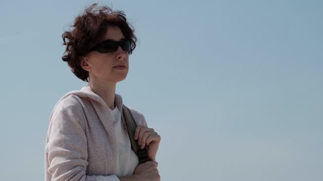 stockvideo's en b-roll-footage met de rijpe vrouw bevindt zich en bekijkt de zon terwijl het lopen in zonnig bos - sunny