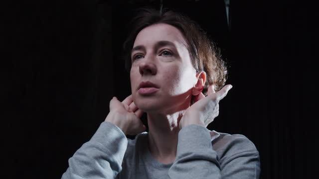 成熟した女性は彼女の耳の後ろに彼女の髪をタックしています - brown hair点の映像素材/bロール