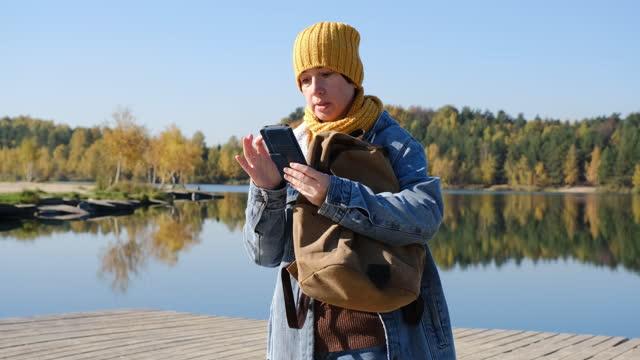 vídeos de stock, filmes e b-roll de mulher madura está usando telefone enquanto caminha na beira do lago de outono - só uma mulher madura