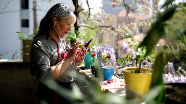 reife frau benutzt smartphone auf der terrasse - frauen über 40 stock-videos und b-roll-filmmaterial