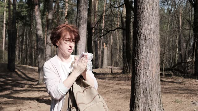 mature woman is wiping her hands in sunny pine forest - one mature woman only stock videos & royalty-free footage