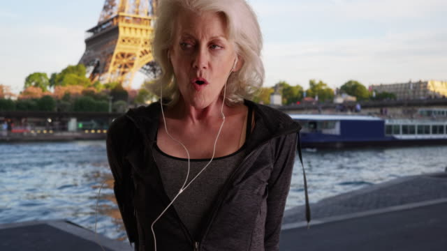 stockvideo's en b-roll-footage met mature woman jogger by the seine warming up for run in the city - jogster