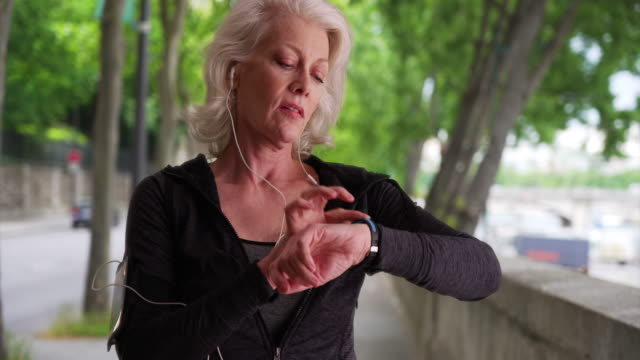 stockvideo's en b-roll-footage met mature woman jogger checks her heart rate - jogster