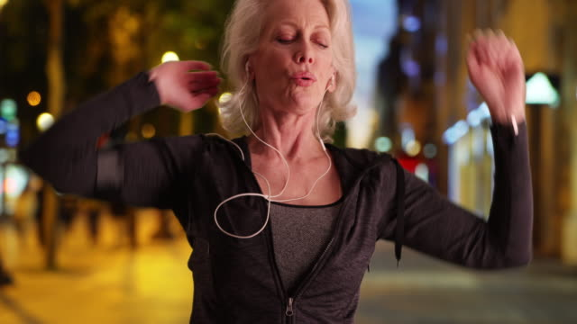stockvideo's en b-roll-footage met mature woman jogger going for night run in the city - jogster
