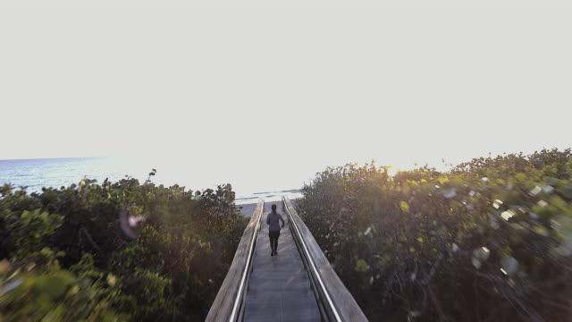 Mature woman jogging along boardwalk toward beach