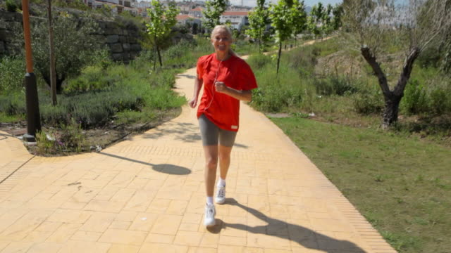 mature woman jogging on a path - only mature women stock videos & royalty-free footage