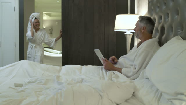 stockvideo's en b-roll-footage met mature woman joining a mature man in bed - dubbel bed