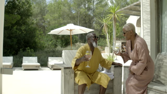 mature woman joins her partner on the terrace - bathrobe stock videos & royalty-free footage