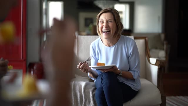 mature woman laughing during family coffee break - ridere video stock e b–roll