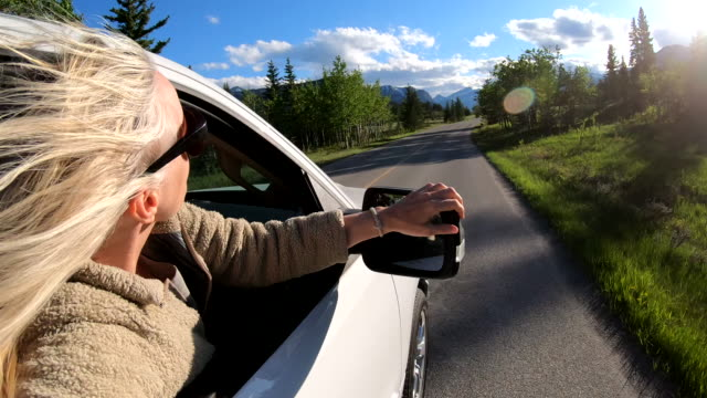 mature woman leans out of car window at sunrise - blonde hair stock videos & royalty-free footage