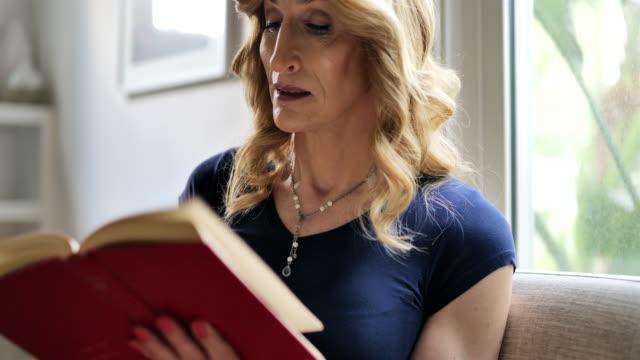 concetti di stile di vita femminile maturo: leggere un libro - letteratura video stock e b–roll