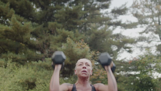 mature woman lifting weights outdoors - grey hair stock videos & royalty-free footage