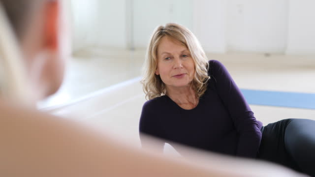 Mature woman listening to friend at yoga class