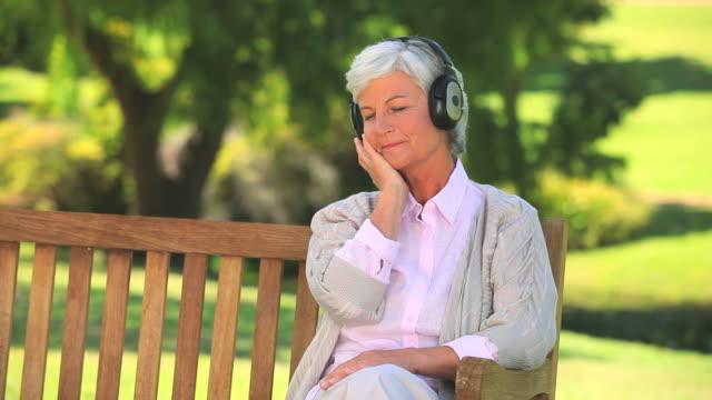 vidéos et rushes de mature woman listening to music outside / cape town, western cape, south africa - une seule femme d'âge mûr
