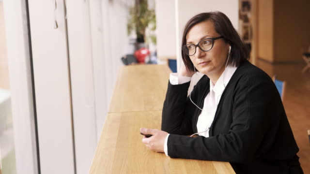 Mature woman listens to podcast
