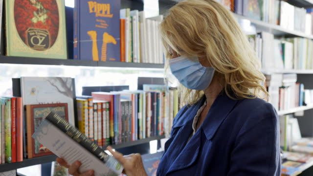 mature woman looking at a book in the bookstore - book shop stock videos & royalty-free footage