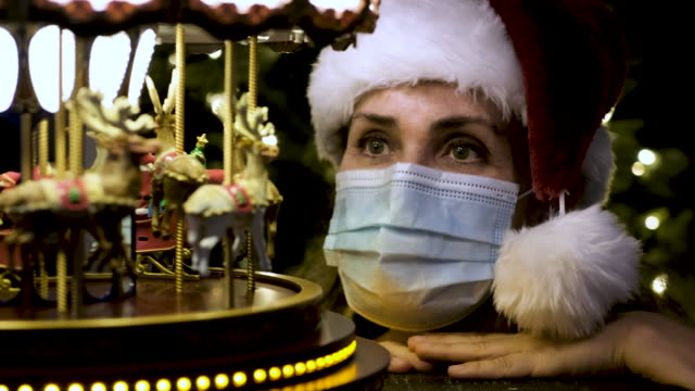 mature woman looking at a toy carrousel wearing a santa hat - roundabout stock videos & royalty-free footage