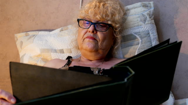 Mature woman looking at an old photo album brings back memories
