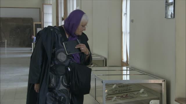 ms mature woman looking at beads in cabinet in national museum of iran, tehran, iran - skåp med glasdörrar bildbanksvideor och videomaterial från bakom kulisserna