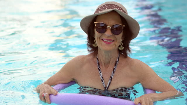 mature woman looking at camera in the swimming pool - 70 79 years stock videos and b-roll footage