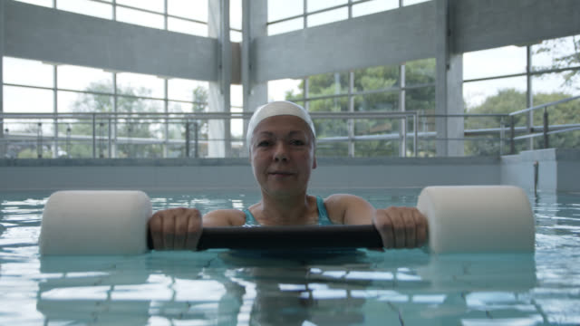 mature woman looking at camera while exercising during hydrotherapy at a physical rehab clinic - hydrotherapy stock videos & royalty-free footage