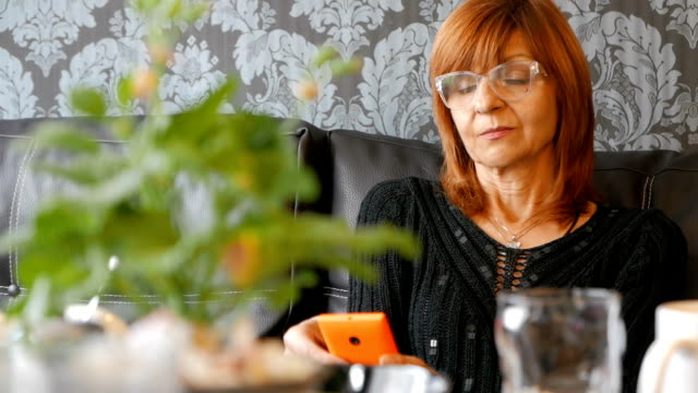 Mature woman looking at her smart phone
