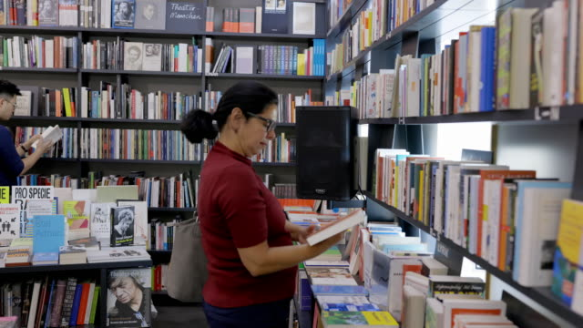 mature woman looking at the books at bookstore - book shop stock videos & royalty-free footage