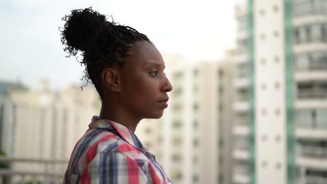 mogen kvinna tittar på utsikt i lägenhetens veranda - förutsäga bildbanksvideor och videomaterial från bakom kulisserna