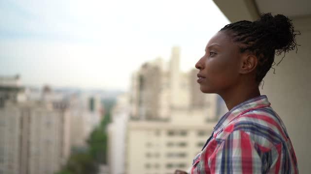 vidéos et rushes de femme mûr regardant la vue dans le porche de l'appartement - regarder ailleurs