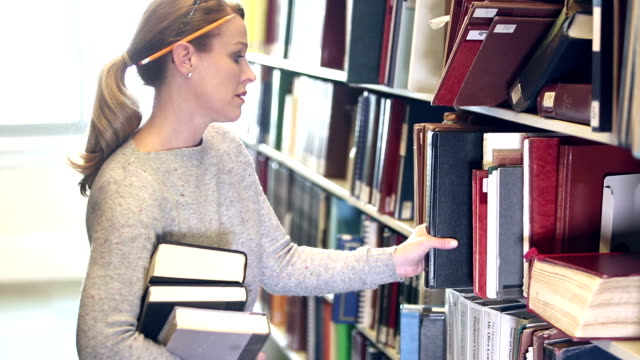 mature woman looking for books in library - bibliotecario video stock e b–roll