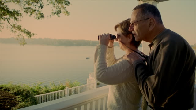 Mature woman looking out from deck with binoculars / senior man joining her and nuzzling her neck